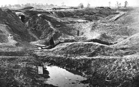 The Crater as it appeared in 1865. The Union soldier seated at the end of the tunnel gives an idea of the size of the Crater.  National Archives.